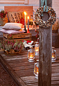 Wreath of bird seed hung on wooden pillar in front of lanterns on floor, cushions on wooden crate and candles on terrace
