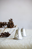 Two vintage-style bells and pine cones on white blanket