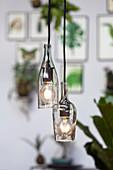 Zwei aufgeschnittene Glasflaschen als Lampenschirme
