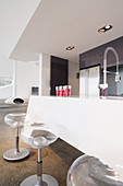 Transparent barstools at white kitchen counter