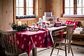 Christmas decorations on table with drawer in rustic cabin parlour