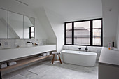 Free-standing bathtub below window and double washstand in spacious bathroom