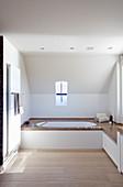 Eingebaute Badewanne mit Natursteinrand und Ablage in minimalistischem Badezimmer