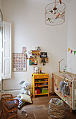 Cot in simple nursery with wooden floor
