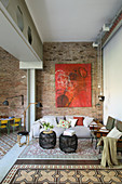 Large red painting on brick wall in living room