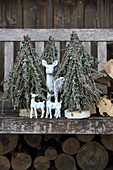 Christmas tree ornaments made from branches covered in lichen on bench