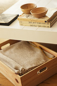Blanket in wooden box under books and bowls on coffee table