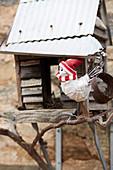 Winterlich gekleidete Vogelfigur vor Vogelhäuschen
