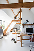 Computer workstation in open-plan attic room with white floor