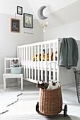 Stofftiere im Korb auf Rädern, weißer Kinderstuhl und Babybett