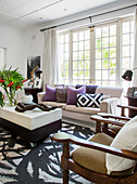 Armchair, coffee table and sofa with scatter cushions in front of lattice French windows in living room