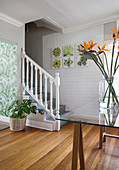 Vase of flowers on glass table and foot of staircase in foyer with whitewashed brick wall