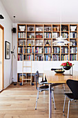 Shelf wall with library ladder in natural tones in the dining room