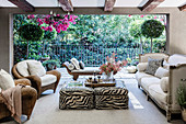 Rattan armchair, ottoman with animal print, antique sofa and day bed on living terrace