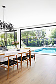 Dining table with designer chairs in front of the window facing the garden with pool