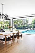 Esstisch mit Designerstühlen vor der Fensterfront zum Garten mit Pool
