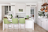 White center block with green bar stools, fitted wardrobes and copper pots in an open kitchen