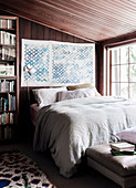 Double bed in the bedroom with dark wood paneling
