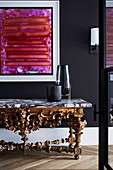 Artwork on black wall and antique console with marble top