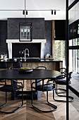 Round, black table with matching chairs in an open kitchen