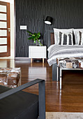 Double bed and white bedside cabinet in bedroom with black wallpaper