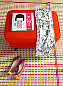 Book and dress on red pouffe and ballet flats on patterned rug