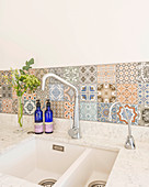 Sink with splashback of Mediterranean-style patterned tiles