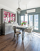 Kitchen dresser with hot-pink cupboard interiors in sunny dining room in shades of grey