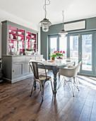 Küchenbuffet mit pinkem Innenleben im sonnigen Esszimmer in Grau