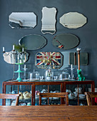 Collection of old mirrors above crockery in display cabinet