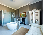 Sofa, oval bathtub and open fireplace in comfortable bathroom