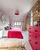 Schlafzimmer mit Backsteinwand und Akzenten in Pink