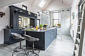Modern country-house kitchen in shades of grey with open roof structure