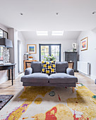 Colourful scatter cushion on grey sofa in classic living room