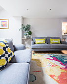 Colourful scatter cushions on grey sofas in simple living room