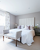 Bed with tall upholstered bed headboard in elegant bedroom