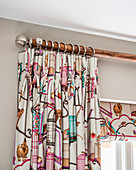 Brightly patterned curtain draped in elegant folds with matching roller blind