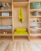 Towels and ornaments on shelves made from plywood panels
