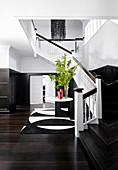 Elegante Eingangshalle mit dunklem Holzboden, Kassettenverkledung und Treppenaufgang