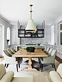 Custom-made dining table with upholstered chairs in an open living room