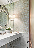 Marble vanity and wall mirror in the bathroom with wallpaper