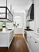 Elegant white kitchen with display cabinet over kitchen island