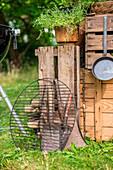 Grillrost vor Outdoor-Küche aus Holzkisten im sommerlichen Garten