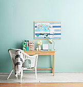 Desk in front of light blue wall with blue pin board