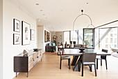 Sideboard und Esstisch mit Stühlen in offenem Wohnraum, Fensterfront zu Balkon