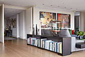 Collection of vases and designer lamp on top of bookcase against back of grey sofa in front of large photos on wall