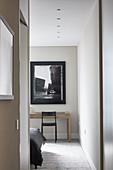 View of desk and chair in bedroom seen through open doorway