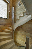 Staircase with glass balustrade in chalet with wood-panelled walls