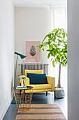 Side table, standard lamp, yellow armchair and potted tree in corner of room