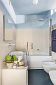 Washstand with countertop sink and bathtub in bathroom with pale wall tiles and sky-blue ceiling